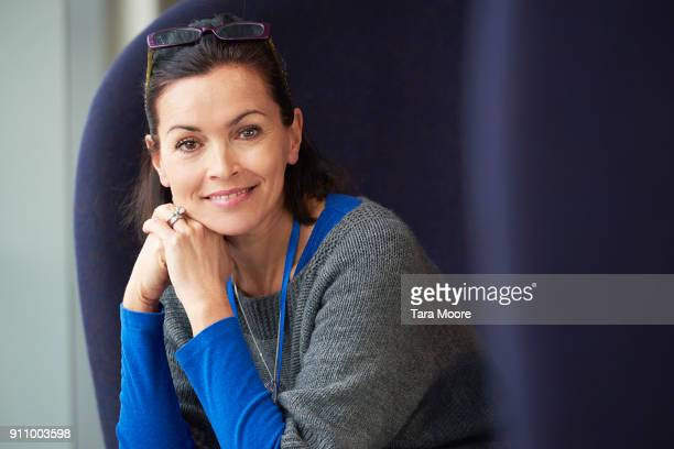 portrait of mature woman in office looking to camera - one mature woman only stock pictures, royalty-free photos & images