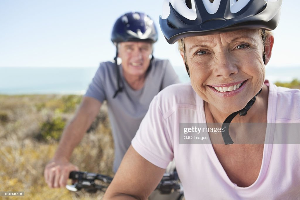 Portrait of mature woman in sports helmet smiling with man in background : Stock Photo