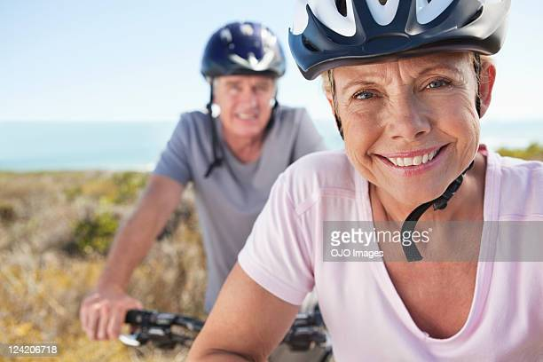 portrait of mature woman in sports helmet smiling with man in background - cycling helmet stock photos and pictures