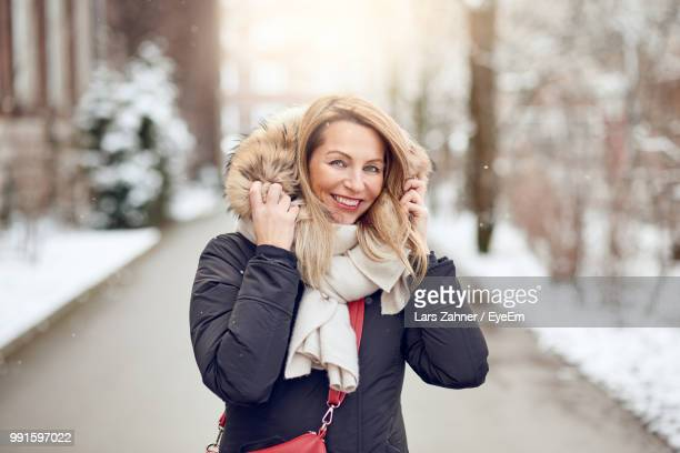 portrait of mature woman in warm clothing standing on street - ropa de invierno fotografías e imágenes de stock