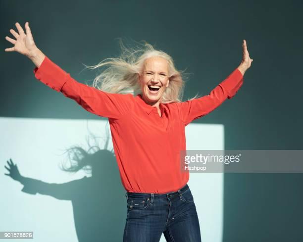 portrait of mature woman laughing - eine seniorin allein stock-fotos und bilder