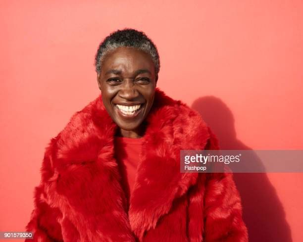 portrait of mature woman laughing - red coat stock pictures, royalty-free photos & images