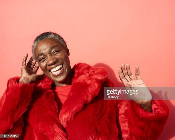 portrait of mature woman laughing - black coat stock pictures, royalty-free photos & images