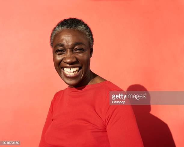portrait of mature woman laughing - black photos et images de collection