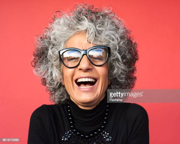 portrait of mature woman laughing - stralende lach stockfoto's en -beelden