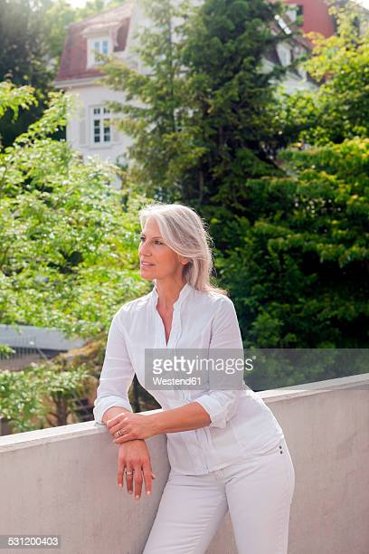 Portrait of mature woman leaning on railing of balcony