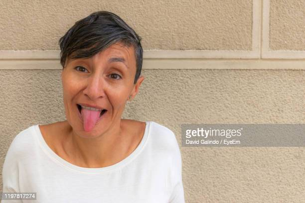 portrait of mature woman making face while standing against wall - caricature stock pictures, royalty-free photos & images
