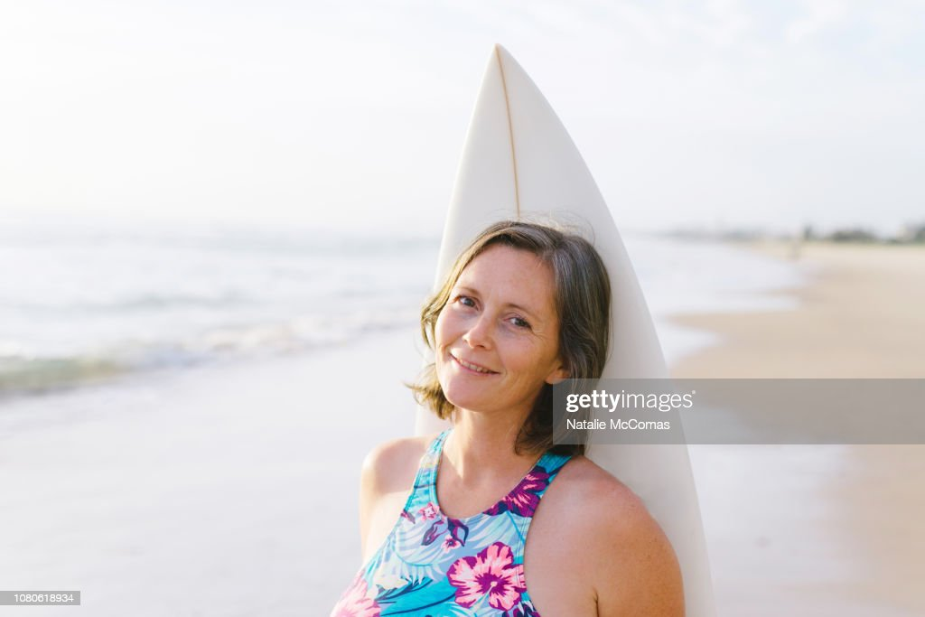 Portrait of mature woman on beach with surfboard : Stock Photo