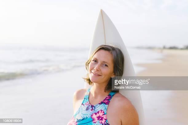 portrait of mature woman on beach with surfboard - showus stock-fotos und bilder