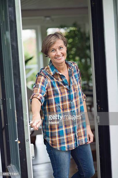 Portrait of mature woman opening door of house