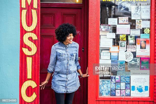 Portrait of mature woman peering from music shop doorway