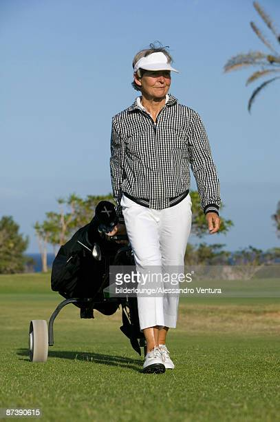 portrait of mature woman pulling golf bag over golf course