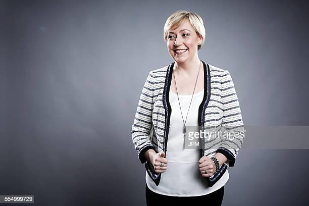 Portrait of mature woman, pulling on jacket edges