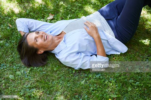 portrait of mature woman relaxing on a meadow - blue blouse stock pictures, royalty-free photos & images