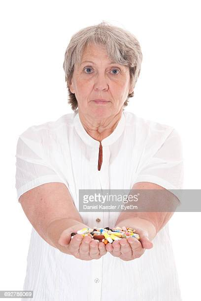 Portrait Of Mature Woman Showing Pills While Standing Against White Background