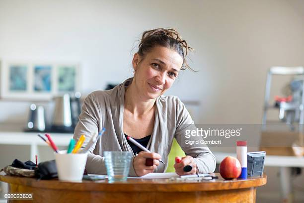 portrait of mature woman sitting at desk, holding pen - sigrid gombert foto e immagini stock