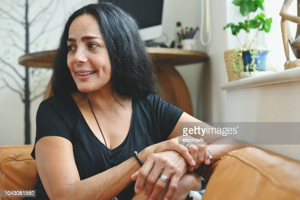 portrait of mature woman sitting at home - puerto rican ethnicity stock pictures, royalty-free photos & images