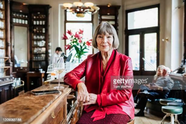 portrait of mature woman sitting at restaurant bar - seniorinnen stock-fotos und bilder