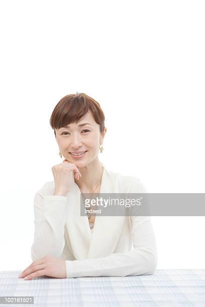 portrait of mature woman, sitting at table - 中年の女性一人 ストックフォトと画像