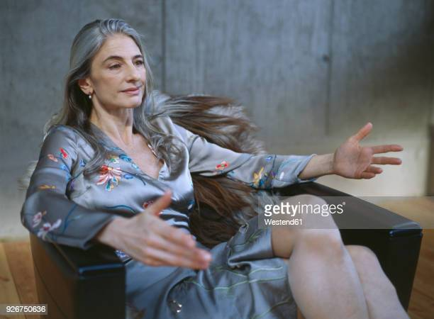 portrait of mature woman sitting in armchair gesturing - beautiful dominant women stock pictures, royalty-free photos & images