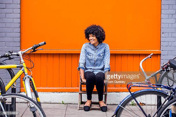 portrait of mature woman sitting in front of orange wall - sitting stock pictures, royalty-free photos & images