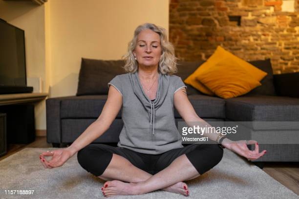 portrait of mature woman sitting on carpet in the living room meditating - cushion stock photos and pictures