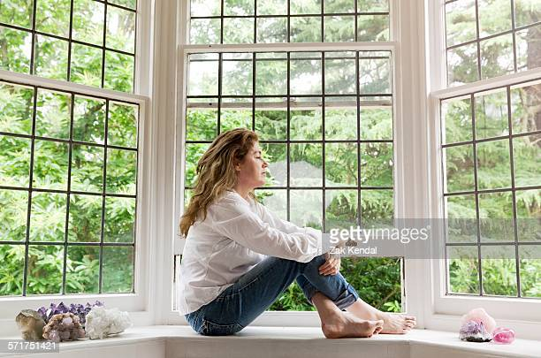 portrait of mature woman sitting on living room windowsill looking out of window - erker stockfoto's en -beelden