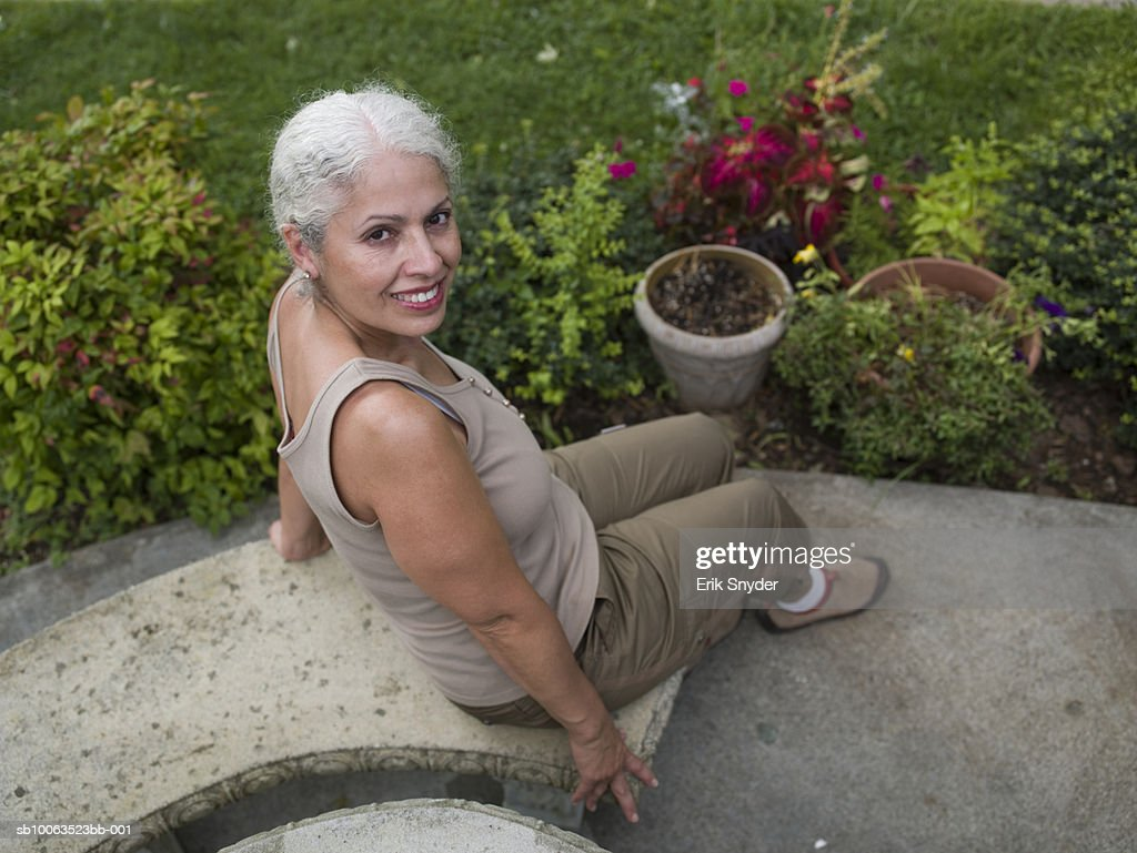 Portrait Of Mature Woman Sitting On Stone Bench In Garden ...