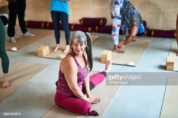 portrait of mature woman sitting on yoga mat smiling - one woman only stock pictures, royalty-free photos & images