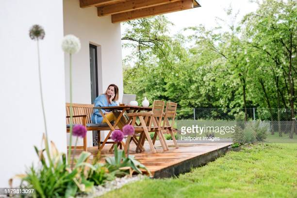 portrait of mature woman sitting outdoors on terrace, using laptop and smartphone. - building terrace stock pictures, royalty-free photos & images