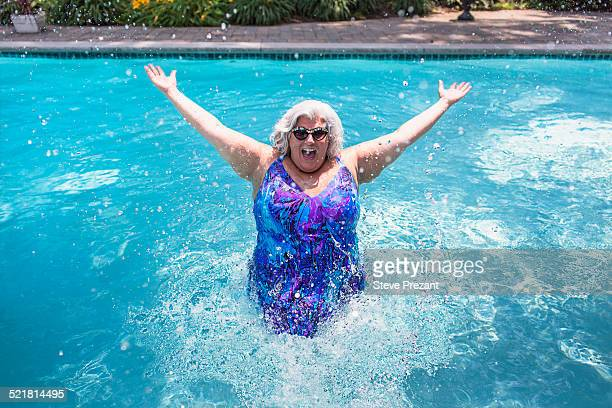 portrait of mature woman splashing about in swimming pool - chubby swimsuit stock photos and pictures