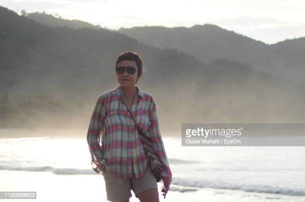 portrait of mature woman standing at beach - oppie muharti stock pictures, royalty-free photos & images