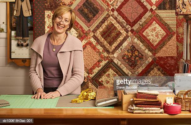 Portrait of mature woman standing behind counter in textile shop