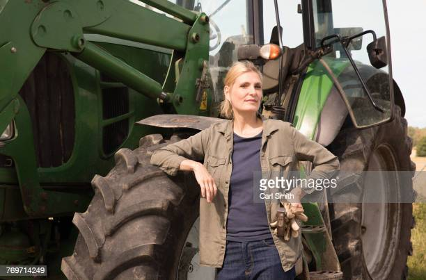 Portrait of mature woman standing by tractor on sunny day
