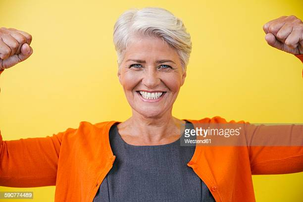 Portrait of mature woman standing like superwoman in front of a yellow wall