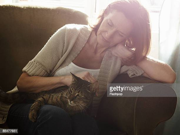 portrait of mature woman stroking cat - stroking stock pictures, royalty-free photos & images