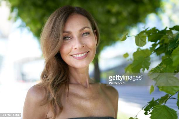 portrait of mature woman, tree in the background - off shoulder stock pictures, royalty-free photos & images