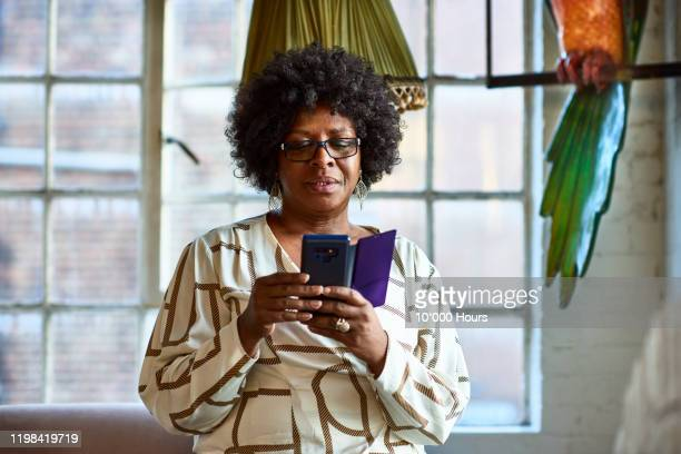 portrait of mature woman using smartphone at home - mature adult stock pictures, royalty-free photos & images