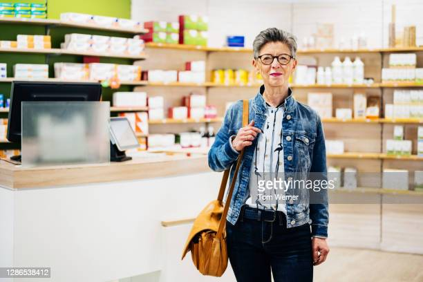 portrait of mature woman visiting her local pharmacy - consumerism stock pictures, royalty-free photos & images