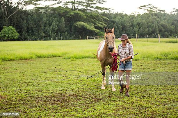 Portrait of mature woman walking with horse in field