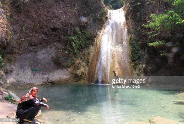 Portrait Of Mature Woman Wearing Hijab While Sitting Against Waterfall
