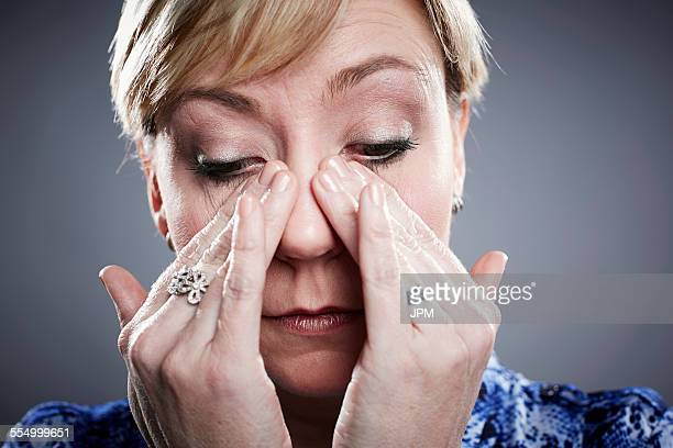 Portrait of mature woman, wiping away tears from eyes
