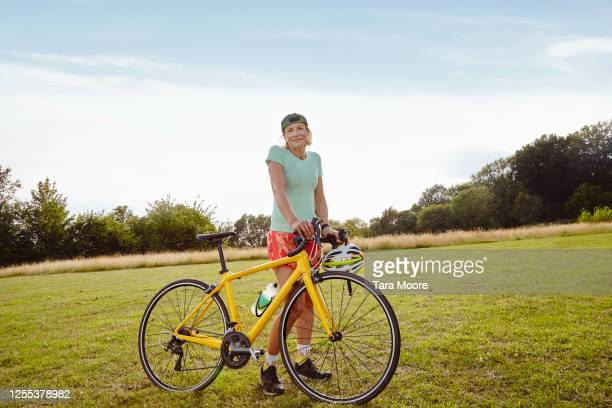 portrait of mature woman with bicycle - bicycle stock pictures, royalty-free photos & images
