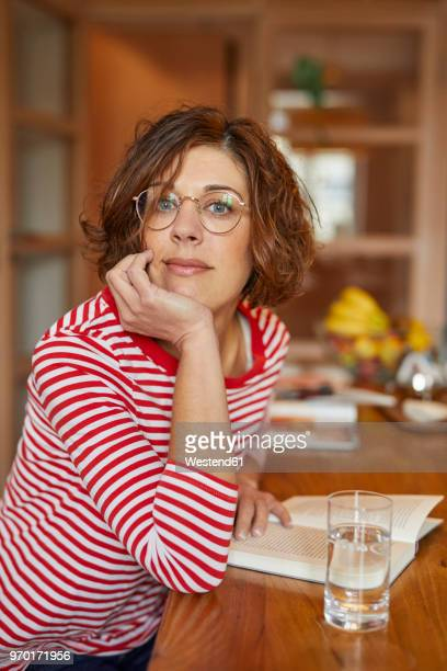 Portrait of mature woman with book at home