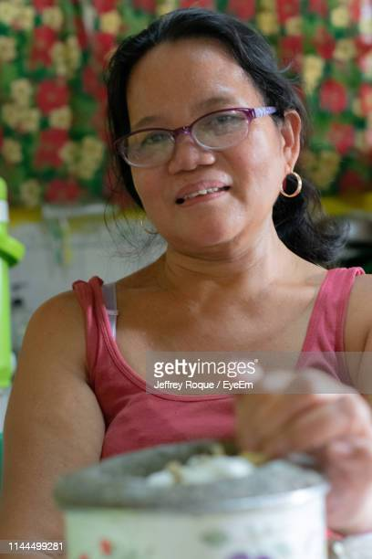 Portrait Of Mature Woman With Food Sitting At Home