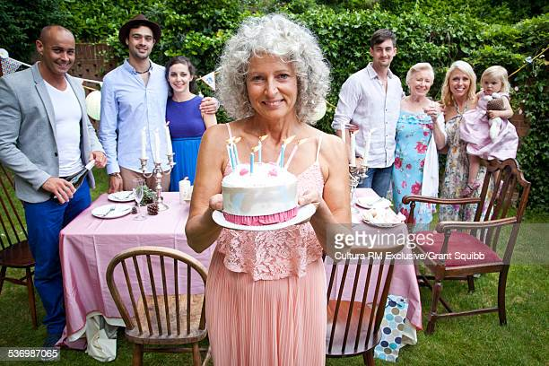 Portrait of mature woman with friends and family at birthday party in garden
