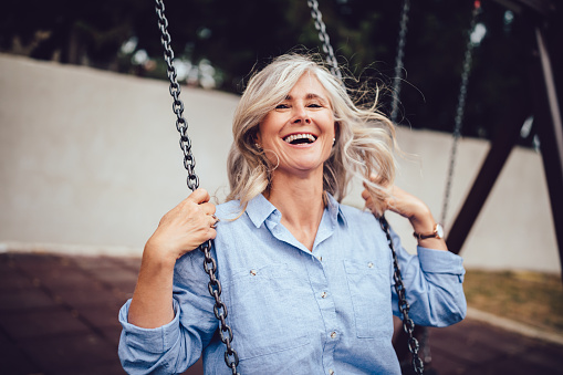 Portrait of mature woman with gray hair sitting on swing 986698776