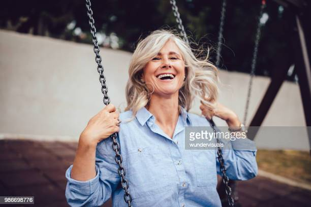 portrait of mature woman with gray hair sitting on swing - active senior woman stock photos and pictures