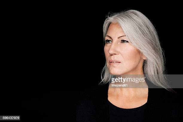 portrait of mature woman with grey hair in front of black background - graues haar stock-fotos und bilder