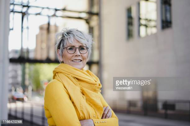 portrait of mature woman with grey hair wearing glasses and yellow clothes - kurzes haar stock-fotos und bilder